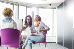 Businesswomen discussing in creative office Stock Images