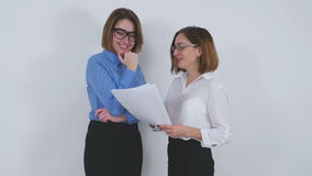 Businesswomen discussing a document and shaking. Businesswomen with glasses are discussing a document then agree with it and shaking hands and smile looking to stock video