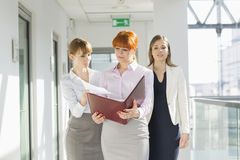Businesswomen discussing over documents at office hallway stock photos
