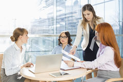 Businesswomen discussing over documents at table in office Royalty Free Stock Image