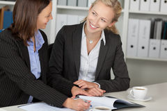 Businesswomen  Discussing Over File At Desk Royalty Free Stock Photo