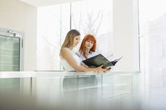 Businesswomen discussing over file folder in office Stock Photos