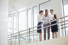 Businesswomen discussing over paperwork against railing Stock Image