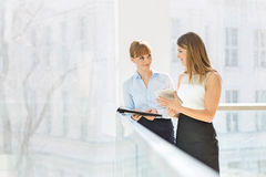 Businesswomen discussing over tablet PC while standing by railing in office Stock Image