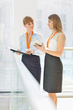 Businesswomen discussing over tablet PC while standing by railing in office Royalty Free Stock Photos