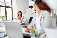 Businesswomen discussing papers at office Royalty Free Stock Images