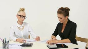 Businesswomen discussing paperwork at office desk. Businesswomen discussing paperwork at office desk stock footage