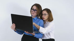 Businesswomen discussing a project on laptop. Businesswomen with glasses holds a laptop and discusses some project typing on keyboard stock video