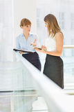 Businesswomen discussing while standing by railing in office Royalty Free Stock Photos