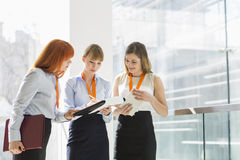Businesswomen doing paperwork by railing in office Royalty Free Stock Photos