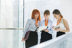 Businesswomen doing paperwork by railing in office Stock Images