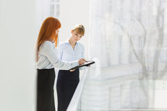 Businesswomen doing paperwork while standing by railing in office Royalty Free Stock Images