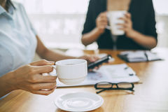 Businesswomen drinking coffee in office Royalty Free Stock Photography