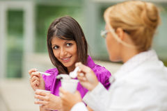 Businesswomen eating yogurt. Two young business women eating yogurt outdoors Royalty Free Stock Image