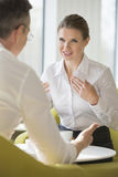 Businesswomen explaining to male colleague at office lobby Stock Images