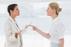 Businesswomen fighting in office Royalty Free Stock Image