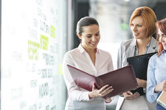 Businesswomen with file folders discussing in office corridor Royalty Free Stock Photos