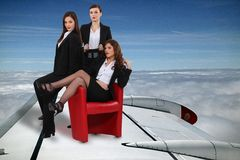 Businesswomen flying plane Stock Image