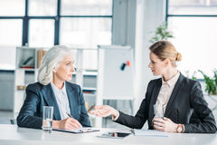 Businesswomen gesturing and discussing business project on meeting in office Royalty Free Stock Image