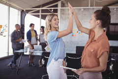 Businesswomen giving high five with colleagues in background. Cheerful businesswomen giving high five with colleagues in background stock photos