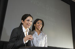 Businesswomen Giving A Lecture At Conference. Happy businesswomen giving a lecture at conference Stock Image