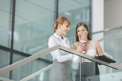 Businesswomen gossiping while having coffee on steps in office Stock Photo