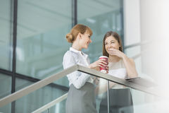 Businesswomen gossiping while having coffee on steps in office Stock Photography