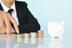Businesswomen hand walking in coin and white piggy bank Stock Photography