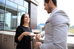 Businesswomen having break on office terrace outdoor drinking coffee talking. Royalty Free Stock Image