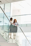 Businesswomen having coffee while standing on steps in office Stock Photos