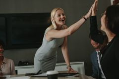 Businesswomen high five in a board room meeting. Happy business professionals having meeting in office conference room stock photos
