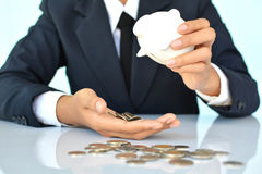 Businesswomen holding coin and white piggy bank Stock Image
