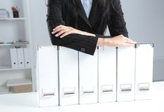 Businesswomen holding data files on binder shelves background.  Royalty Free Stock Images