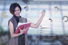 Businesswomen holding document and writing graph digital Stock Photography