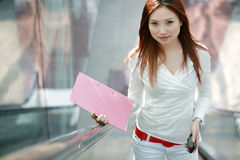Businesswomen holding folder on escalator Stock Photography