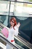 Businesswomen holding folder on escalator Stock Photo
