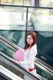 Businesswomen holding folder on escalator Royalty Free Stock Photo