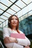 Businesswomen holding folder and wave on escalator Stock Photo