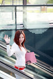 Businesswomen holding folder and wave on escalator Stock Images
