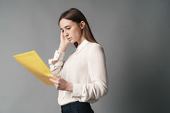 Businesswomen holds documents in her hand. One. Isolated on gray background royalty free stock photo