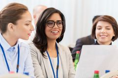 Businesswomen at international business conference. Business, people and education concept - businesswoman showing document to colleague at international royalty free stock photography
