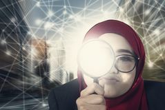 Businesswomen keep searching using her magnifier over abstract connection line background Stock Photos