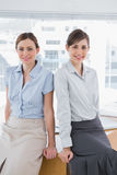 Businesswomen leaning on desk Stock Photography