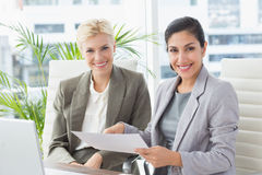 Businesswomen looking at camera and reading files Royalty Free Stock Image