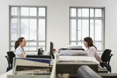 Businesswomen Looking At Each Other While Sitting In Office Royalty Free Stock Photos