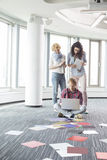 Businesswomen looking at male colleague using laptop on floor in creative office Stock Photos