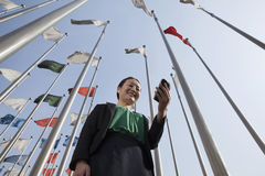 Businesswomen looking at mobile phone with flags in background. royalty free stock images