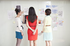 Businesswomen Looking At Wall of Ideas Royalty Free Stock Images