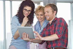 Businesswomen with male colleague using tablet PC in creative office Royalty Free Stock Images