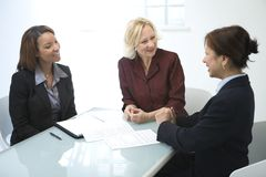 Businesswomen in a meeting. Three businesswomen in a meeting, discussing some documents royalty free stock image
